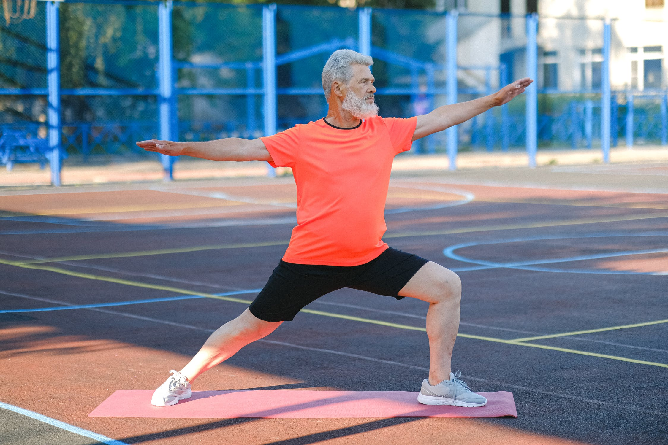 Older Man Bearded Stretching on Tennis Court in Bright Shirt